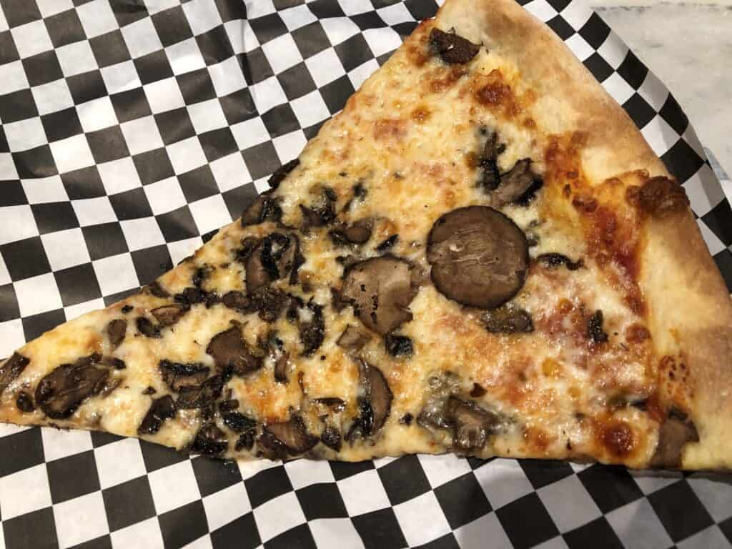 Slice of mushroom and cheese pizza from Secret Pizza at Cosmopolitan
