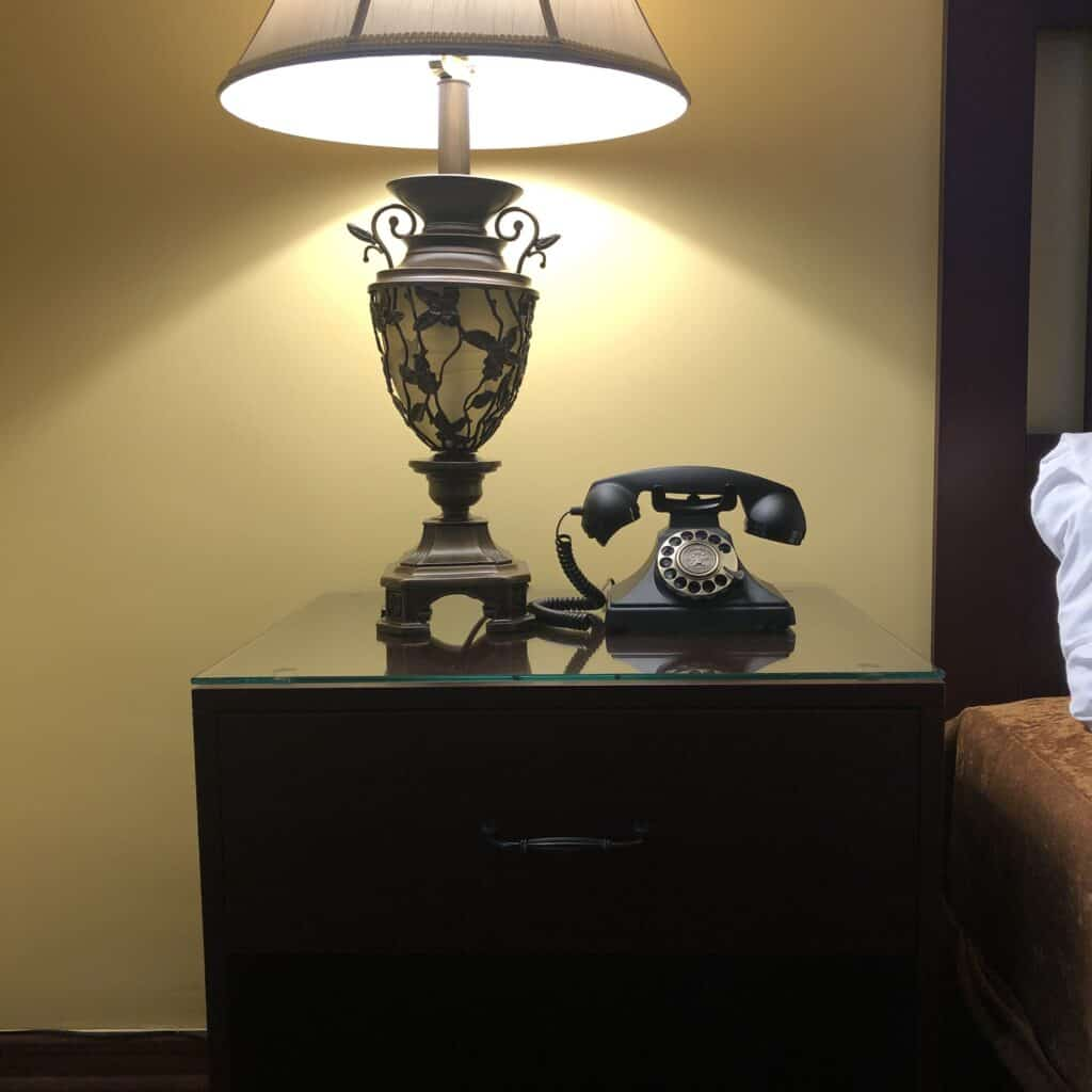 Vintage lamp and rotary phone atop nightstand