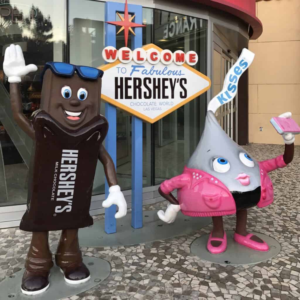 """Photo opp depicing a life like Hershey's bar and a Hershey's Kiss in front of a Hershey's sign intended to look like the """"welcome to Las Vegas Sign""""."""