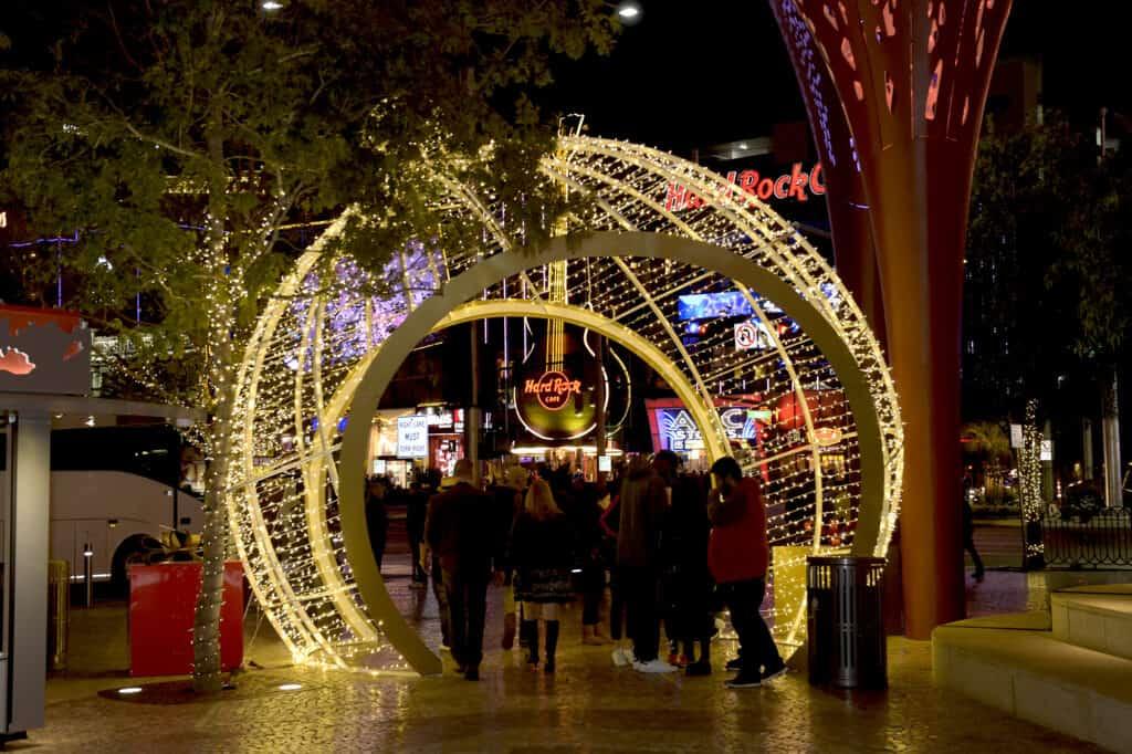 People walking through an illuminated ornament