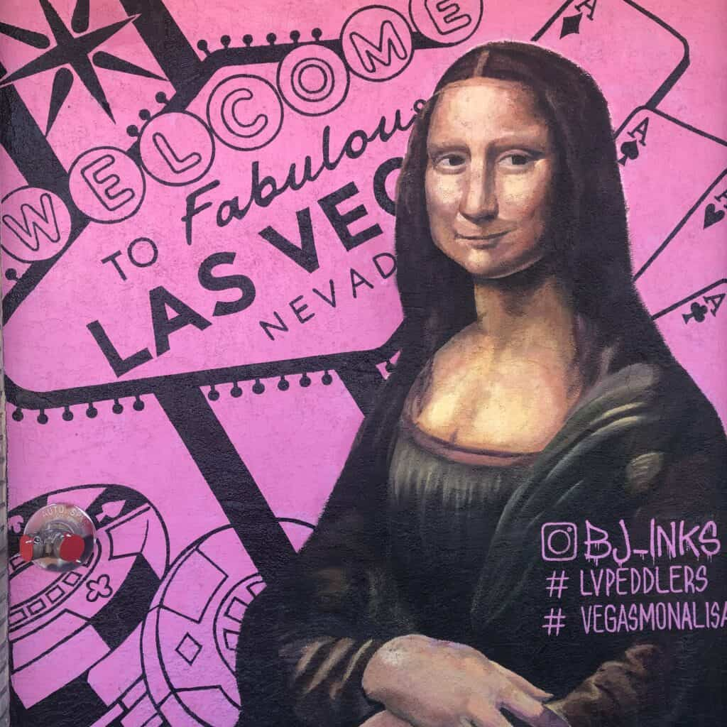 Mona Lisa mural with the Welcome to Las Vegas Sign in the background