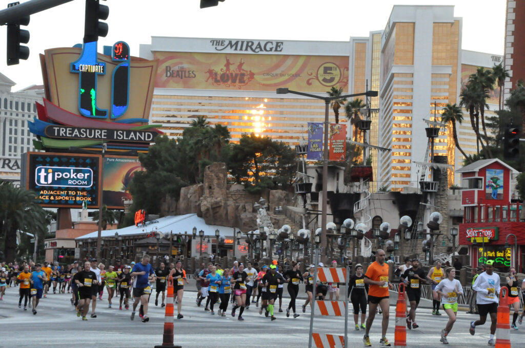 Runners running down the Las Vegas Strip with Mirage in the background