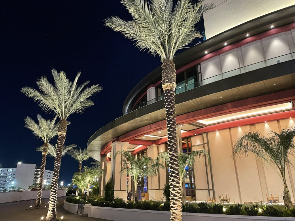 Resorts World exterior with illuminated palm trees
