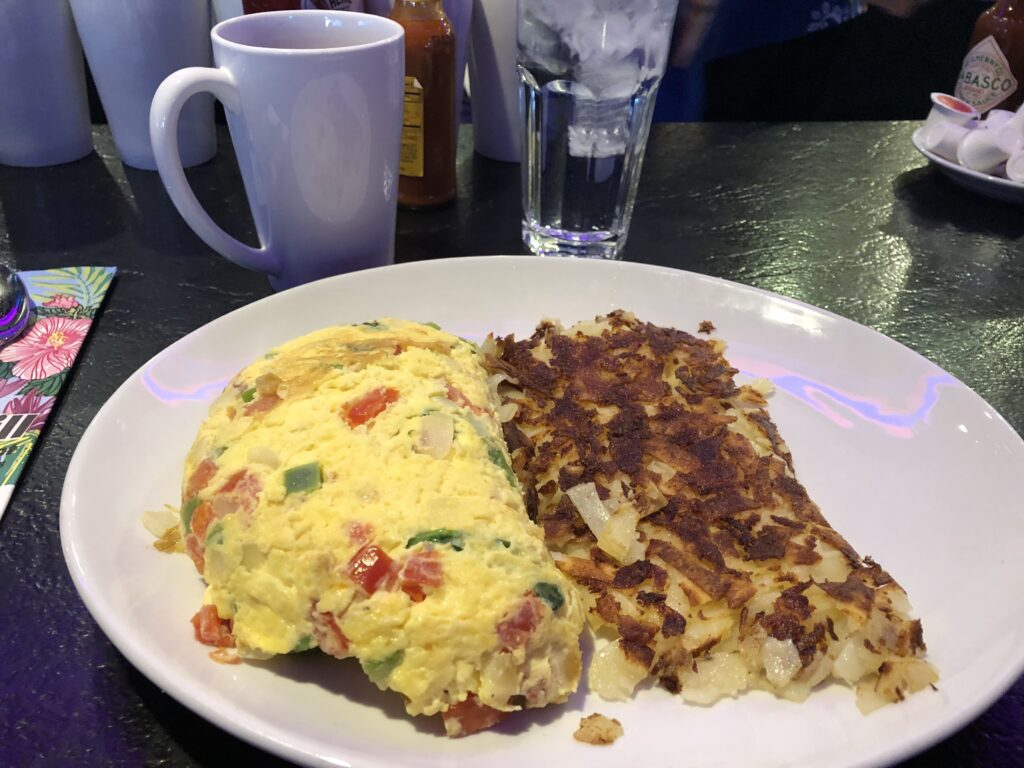 Omelet with peppers and ham and hash browns on a plate
