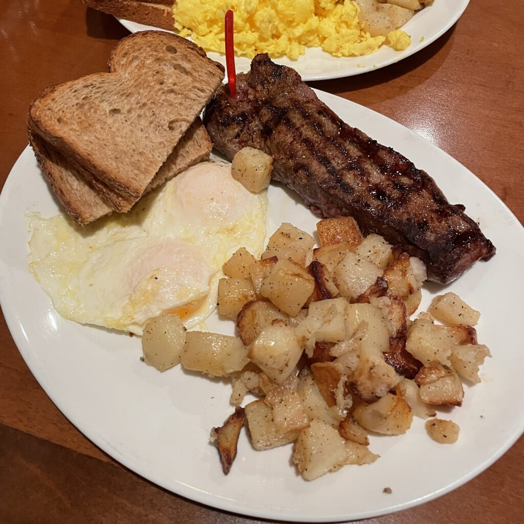 Steak, Eggs over easy, toast, and breakfast potatoes on a plate