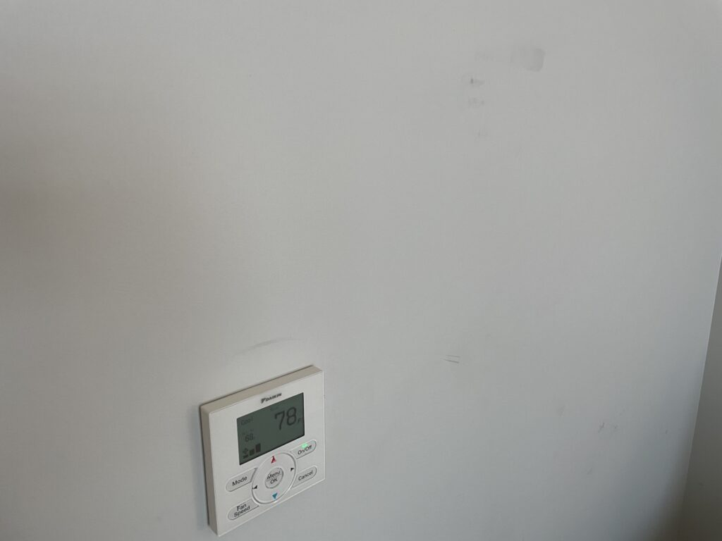 Scuffs on the wall surrounding a thermostat
