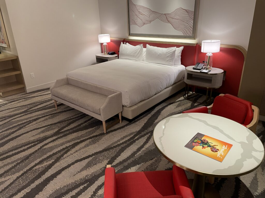 Bed and Living area in a Resorts World Conrad Room